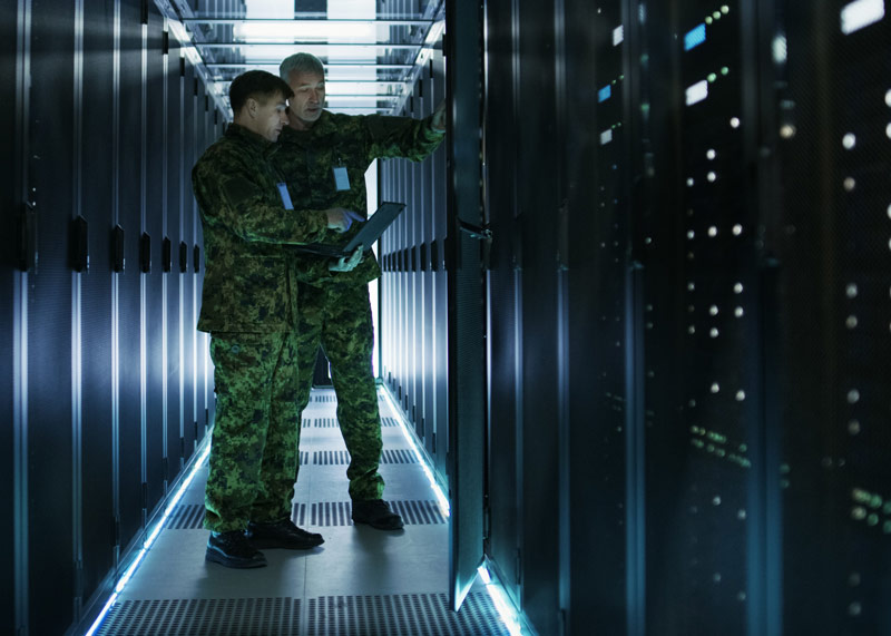 Two Army Personnel Discussing in a Server Room